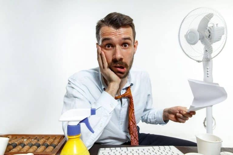 Spocony mężczyzna w upalny dzień w biurze