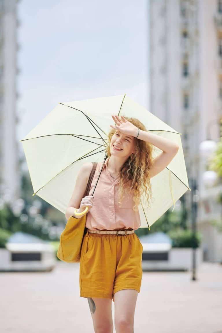 Kobieta chowająca się pod parasolem w upalny dzień